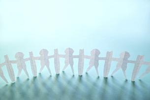 青い紙の上に立てた新型コロナ対策で衝立を挟んで繋がる人々の切り紙。上にコピースペース。の写真素材 [FYI04779936]