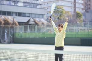 テニスコートで喜ぶ女性の写真素材 [FYI04780157]