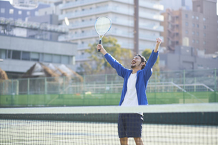 テニスコートで喜ぶ男性の写真素材 [FYI04780158]