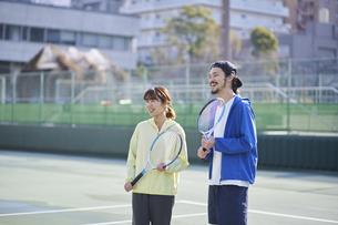 テニスコートで笑う男女の写真素材 [FYI04780160]