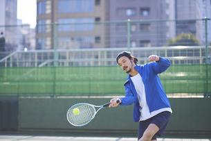 テニスボールを打ち返す男性の写真素材 [FYI04780162]