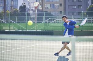テニスボールを打ち返す男性の写真素材 [FYI04780165]