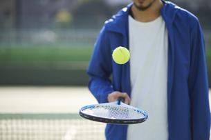ラケットの上でボールを弾ませる男性の写真素材 [FYI04780171]
