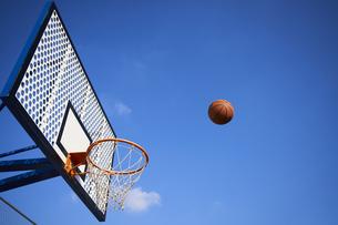 青空とバスケットゴールとシュートされるボールの写真素材 [FYI04780192]