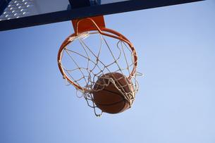 青空とバスケットゴールとシュートされるボールの写真素材 [FYI04780195]