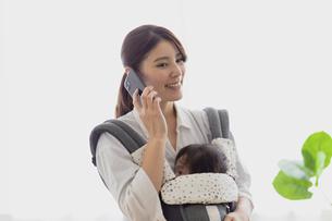 赤ちゃんを抱っこしながらスマホを見る母の写真素材 [FYI04780206]