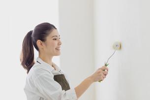 壁のペンキを塗る女性の写真素材 [FYI04780218]