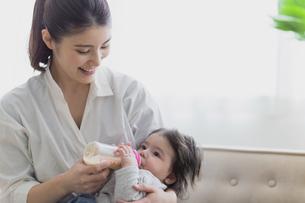 赤ちゃんにミルクをあげる女性の写真素材 [FYI04780236]