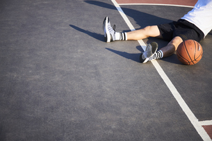 バスケットコートで休憩する男性の写真素材 [FYI04780239]