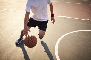バスケットボールをドリブルする男性の写真素材 [FYI04780240]