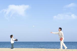 砂浜で野球をする親子の写真素材 [FYI04780293]