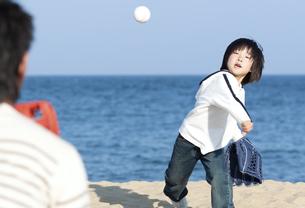 砂浜で野球をする親子の写真素材 [FYI04780294]