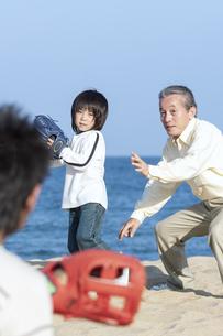 砂浜で野球をする三世代家族の写真素材 [FYI04780303]