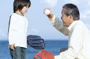 孫に野球を教える祖父の写真素材 [FYI04780314]