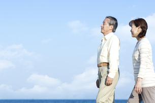 海辺を歩くシニア夫婦の写真素材 [FYI04780323]
