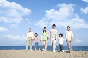 砂浜を歩く三世代家族の写真素材 [FYI04780325]