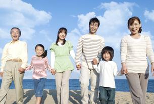 砂浜を歩く三世代家族の写真素材 [FYI04780327]