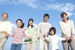 手を繋ぐ笑顔の三世代家族の写真素材 [FYI04780330]