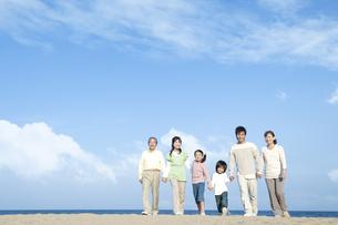 砂浜を歩く三世代家族の写真素材 [FYI04780332]