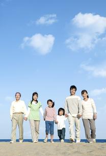 砂浜を歩く三世代家族の写真素材 [FYI04780333]