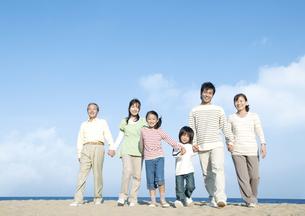 砂浜を歩く三世代家族の写真素材 [FYI04780334]