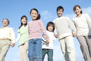 手を繋ぐ笑顔の三世代家族の写真素材 [FYI04780338]