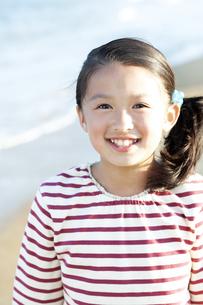 砂浜に立つ笑顔の女の子の写真素材 [FYI04780343]