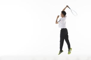 ジャンプしてリターンを打つ男性の写真素材 [FYI04780365]