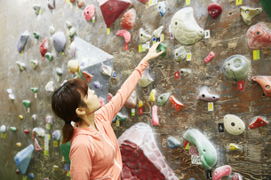 ボルダリングで登るルートを考える女性の写真素材 [FYI04780419]
