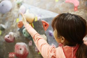 ボルダリングで次のホールドに手を伸ばす女性の写真素材 [FYI04780421]