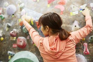 ボルダリングで次のホールドに手を伸ばす女性の写真素材 [FYI04780422]