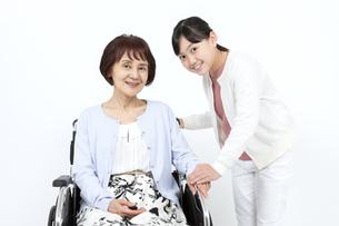 車椅子に乗る祖母と寄り添う孫の写真素材 [FYI04780885]