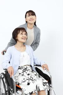 シニア女性の乗った車椅子を押す女性の写真素材 [FYI04780887]