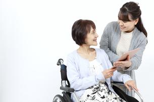 車椅子に乗るシニア女性にタブレットPCを見せる女性の写真素材 [FYI04780888]