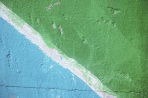 斜めの白い線で青色と緑色を分けたペイントの古いコンクリートの壁の写真素材 [FYI04781089]