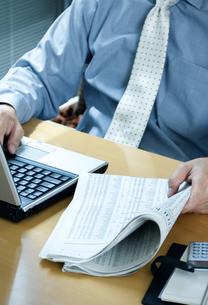 新聞を持ってパソコンをするビジネスマンの写真素材 [FYI04781185]