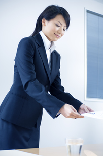 面接官に履歴書を渡す女性の写真素材 [FYI04781221]