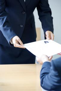 面接官に履歴書を渡す女性の写真素材 [FYI04781264]