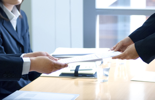 面接官に履歴書を渡す女性の写真素材 [FYI04781265]