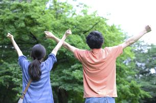 伸びをする男女の後ろ姿の写真素材 [FYI04781624]