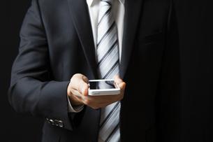 スマートフォンを持つビジネスマンの写真素材 [FYI04781672]
