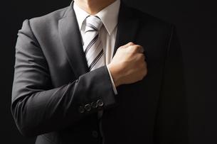拳を胸にあてるビジネスマンの写真素材 [FYI04781694]