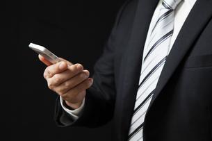 スマートフォンを見るビジネスマンの写真素材 [FYI04781703]