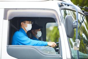 トラックを運転する作業着とマスクを着用した男性の写真素材 [FYI04782630]