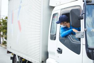 トラックを運転する作業着とマスクを着用した男性の写真素材 [FYI04782631]