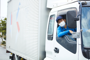 トラックを運転する作業着とマスクを着用した男性の写真素材 [FYI04782632]