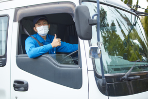 トラックを運転する作業着とマスクを着用した男性の写真素材 [FYI04782633]