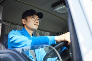 トラックを運転する作業着姿の男性の写真素材 [FYI04782636]