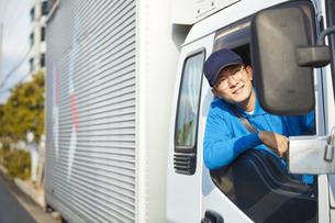 トラックを運転する作業着姿の男性の写真素材 [FYI04782637]