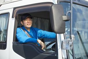 トラックを運転する作業着姿の男性の写真素材 [FYI04782638]